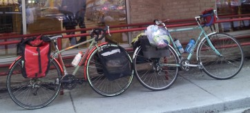 Karen is using one of my favorite capacity expanding tricks: tie a bulging plastic bag on the rack on top of a pannier.